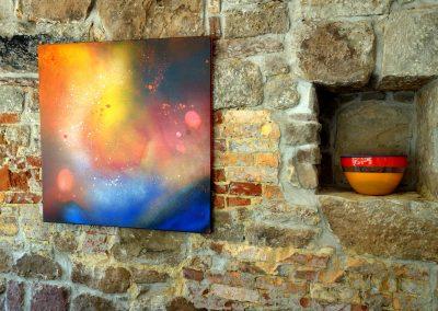 Acrylbild abstrakt mit Universum an einer Steinwand aufgehängt