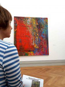 Die Künstlerin Gabriele Bobey betrachtet die abstrakte Malerei von Gerhard Richter.